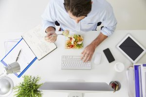 Overhead View Of Businessman Working At Computer In Office Eating Lunch